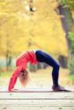 Happy young woman doing yoga in park