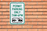 Permit Parking only 7 am to 6 pm sign on a brick wall