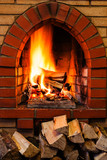 woods pile and burning firewood in brick fireplace