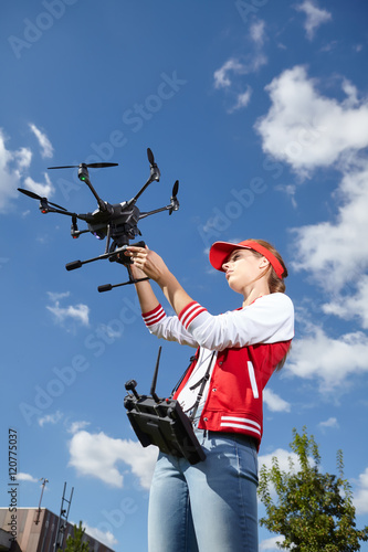 Poster A woman is standing and holding drone. starting procedure