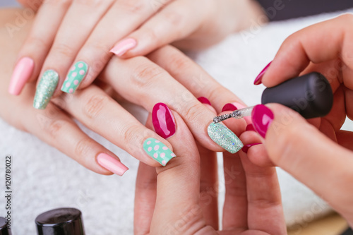Manicure - Beauty treatment photo of nice manicured woman fingernails. Very nice feminine nail art with nice pink and light green nail polish. Polka dots design. © tamara83