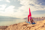 Woman meditating in yoga pose at the sea and mountains