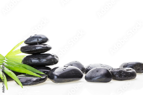 Stack of black wet basalt balancing stones and green leaf, on white background Poster