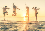 Group of happy people jumping in the sea at sunset.