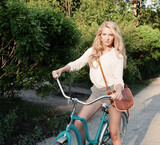 Young sexy blonde girl with long hair with brown vintage bag sits in a vintage bicycle