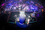 Male DJ performing for crowded nightclub, shot from behind with a fisheye lens