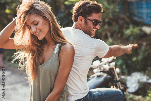 Poster Beautiful young couple on a motorcycle