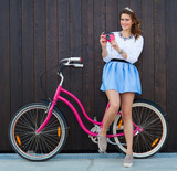 Trendy Fashionable Girl with Vintage Bike on Wooden Background. Pink vintage camera in her hand. Toned Photo. Modern Youth Lifestyle Concept. Close up.