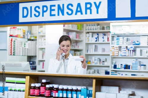 Pharmacist looking at medicine box while talking on phone Poster