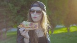 Hipster girl in cap an afternoon snack pizza sitting on the sidewalk