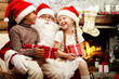 An image of Santa Claus sitting in armchair and two smiling children on his knees holding gifts