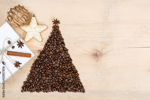 Fotobehang Koffiebonen Christmas tree made from coffee beans and gift box on wooden background. Top view, copy space.Winter holidays concept.