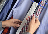 young man choosing a tie from the closet