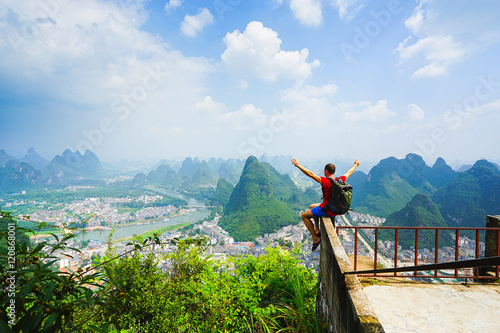 Tuinposter Guilin Hiker sitting on the top of hill with raised hands and enjoing view on the valley with city and mountains. Yangshou, China.