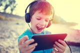Happy little boy with tablet laughing outdoor vintage
