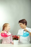 Two cute children watering houseplant isolated