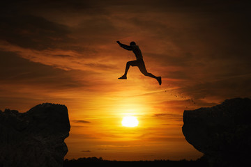 Silhouette of a man jumping over abyss at sunset with copy space © rangizzz