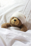 Teddy bear in bed with bandage on head