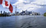 Beautiful Canada flag is waving front of famous Toronto City view