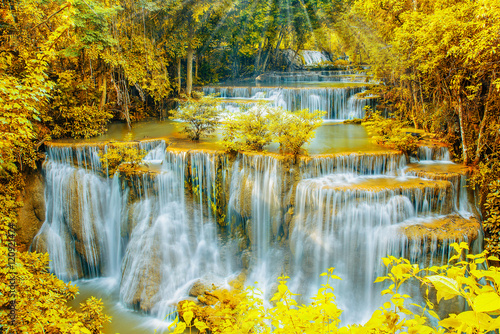 Beautiful  waterfall in autumn forest with ray light.