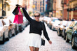 Happy exited woman walking with shopping bag on city street and enjoying shopping