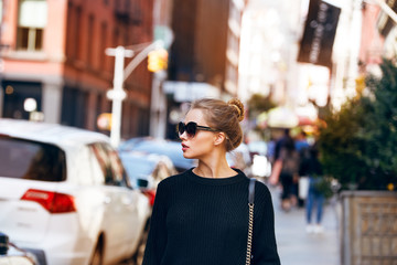 Fashionable woman model walking on New York City street wearing sunglasses and black sweater