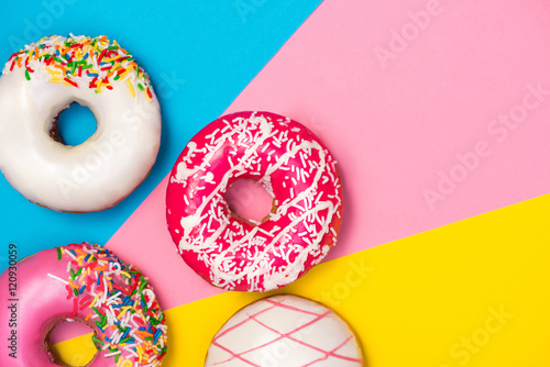 Donuts with icing on colorblock background. Sweet donuts. Poster
