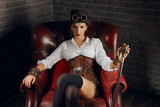 Close-up portrait of a beautiful steampunk girl in lingerie and stockings sitting in old armchair.