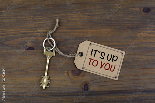Poster Key and a note on a wooden table with text - It's Up To You