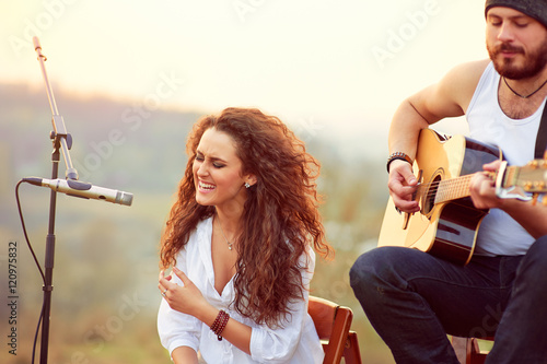 Poster Young beautiful woman singing with a guitar player outdoor.