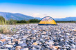 Tent on riverbed rock beach