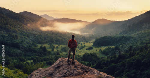 Man standing on top of cliff at sunset