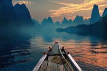 Ein Boot in einem Fluss bei Sonnenuntergang reiten neben einem schönen Berg