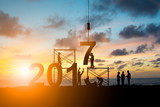 Silhouette employees work as a team to change the 6 to 7, 2017 Happy New Year background