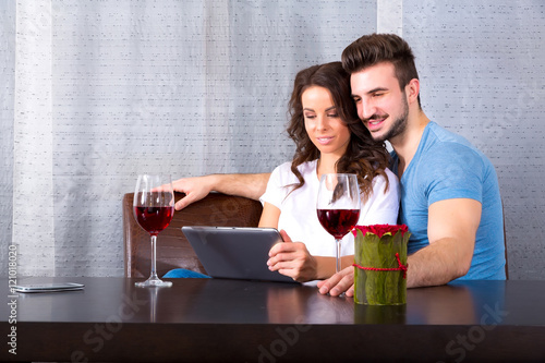Poster Young couple having a romantic evening with a glass of wine.