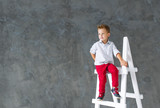 The blond boy sits on a step-ladder.