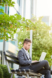 Young businessman sitting at the bench and working on laptop