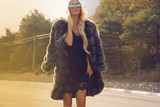 fashion outdoor photo of gorgeous sexy woman with long blond hair in casual clothes and fur posing on road