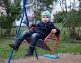 Мальчик трех лет катается на качелях во дворе осенью