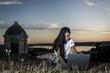 Chica joven con su ordenador portátil chateando en la montaña al lado del río al atardecer. Joven viajera explorando nuevos caminos. Un mundo conectado.