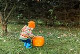 Baby opening lid on Halloween pumpkin