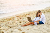 Beautiful romantic couple relaxing on the beach . By browsing on the laptop