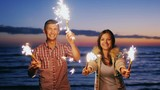 Young couple having fun with fireworks in the hands. Fireworks lit the pair laughing, having a good time. During sunset. Slow motion video
