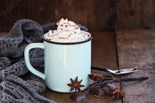 Fotobehang Chocolade Cup of hot cocoa or coffee for Christmas with whipped cream, shaved chocolate, vanilla pod, spices and gray scarf against a rustic background. Shallow depth of field with selective focus on drink.