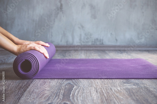 Fotobehang School de yoga Woman rolling her mat after a yoga class