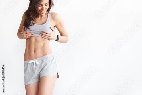 Leinwanddruck Bild Slim tanned woman's body over white background