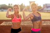 Sporty young women with perfect bodies showing biceps.