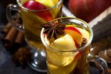 hot apple tea with spices on dark background, top view closeup