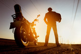 Fototapety Biker with motorbike stands on sunset backdrop sky road