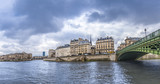 Seine River in Paris on a cloudy day - Panorama with the river Seine, its bridges and the Parisian buildings on its shore. Picture taken in Paris, France.